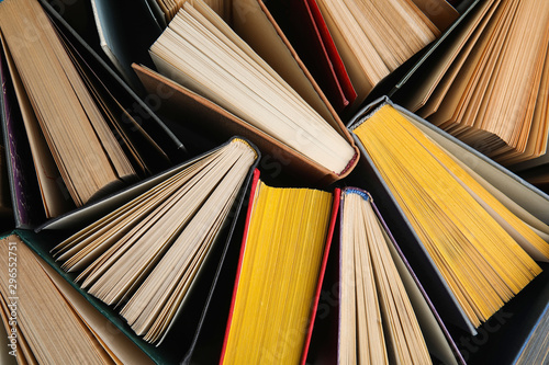 Stack of hardcover books as background, top view