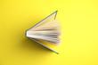 Leinwanddruck Bild - Hardcover book on yellow background, top view