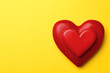 Leinwandbild Motiv Red wooden hearts on yellow background, top view. Space for text