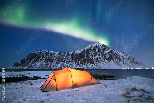 Fond de hotte en verre imprimé Aurore polaire Illuminated tent under a beautiful northern light display on Lofoten islands in Norway
