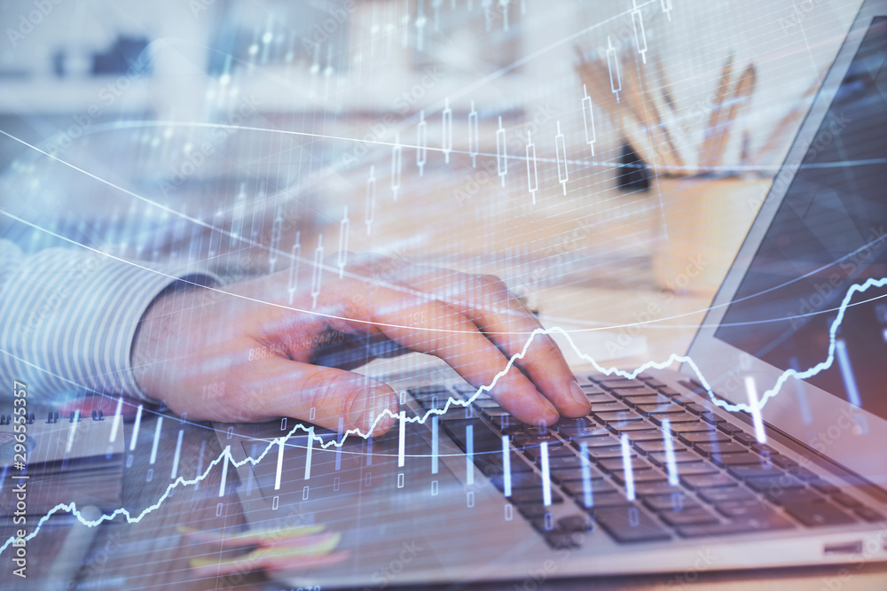 Fototapeta Double exposure of man's hands writing notes with laptop of stock market with forex graph background. Top View. Concept of research and trading.