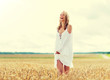 country, nature, summer holidays, vacation and people concept - smiling young woman in white dress on cereal field