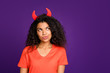canvas print picture - Photo of thoughtful wondered curly wavy girlfriend with horns out of her head thinking on some diabolic things in orange t-shirt isolated vivid purple color background