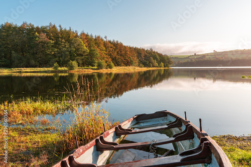 Fotografiet Rowing boat half filled with rain water on the shore of the lake on a misty autumn morning