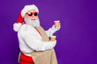 canvas print picture - Profile side view portrait of nice cheerful cheery confident bearded Santa Claus holding in hands two cups cacao sharing giving friend isolated over bright vivid shine vibrant violet lilac background