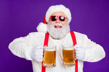 Close-up Portrait Of Nice Glad Cheerful Cheery Positive Bearded Santa Holding In Hands Two Mugs Drinking Beer Having Fun Isolated Over Bright Vivid Shine Vibrant Violet Lilac Background