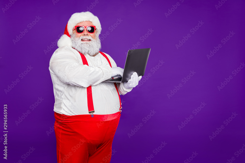 Fototapety, obrazy: Profile side view portrait of his he nice confident cheerful cheery fat thick bearded Santa holding in hands laptop typing e-mail letter isolated on bright vivid shine vibrant violet lilac background