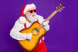 canvas print picture - Portrait of his he nice funny cool cheerful bearded Santa playing guitar having fun midnight entertainment isolated over bright vivid shine vibrant violet lilac background