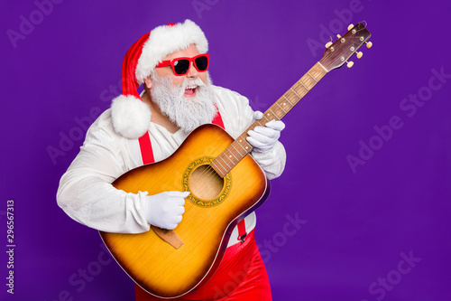 Portrait of his he nice funny cool cheerful bearded Santa playing guitar having fun midnight entertainment isolated over bright vivid shine vibrant violet lilac background - 296567313