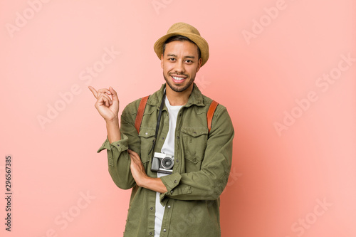 Young filipino traveler man smiling cheerfully pointing with forefinger away Fototapeta