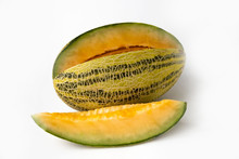 Striped Yellow With Green Stripes An Oblong Melon With A Carved Slice On A White Background.