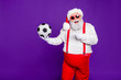 canvas print picture - Photo of grey haired santa holding football ball demonstrating new leather model of football ball for discount x-mas price wear sun specs costume isolated purple background