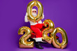 canvas print picture - Full body photo of fat santa man sitting on bike holding big air newyear 2020 numbers balloons congratulating people wear sun specs x-mas costume isolated purple background