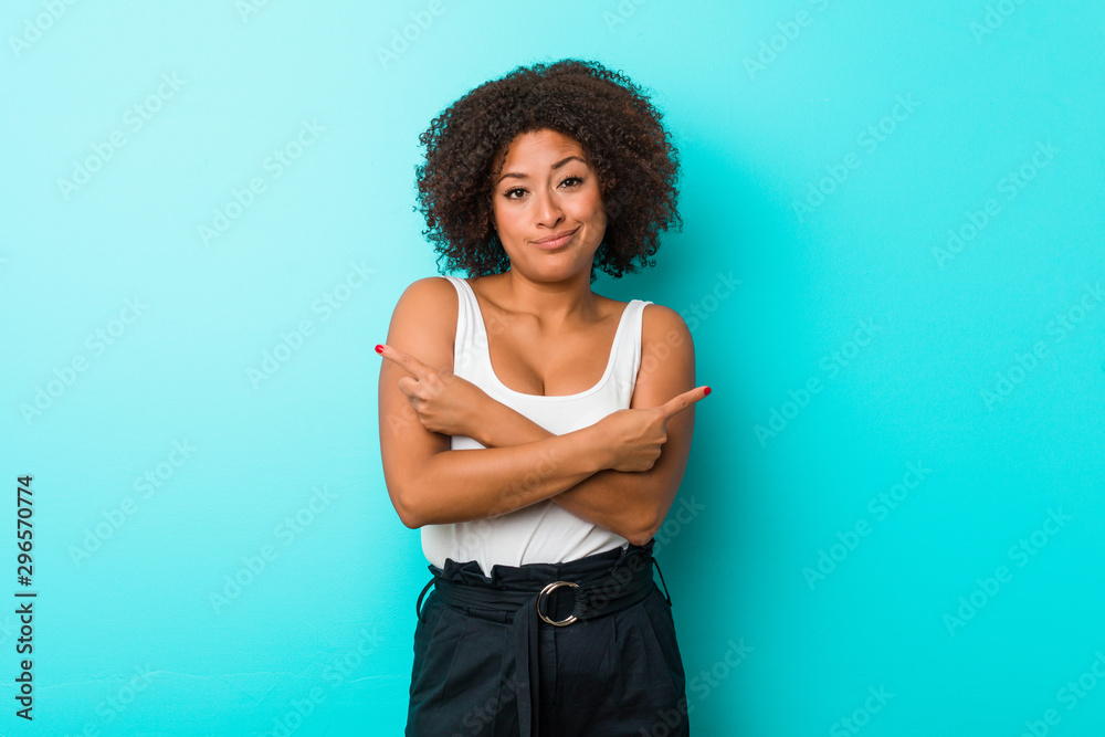 Fototapety, obrazy: Young african american woman points sideways, is trying to choose between two options.