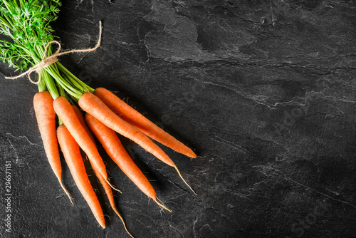 Fotografering Fresh carrot on dark stone table or black background top view.