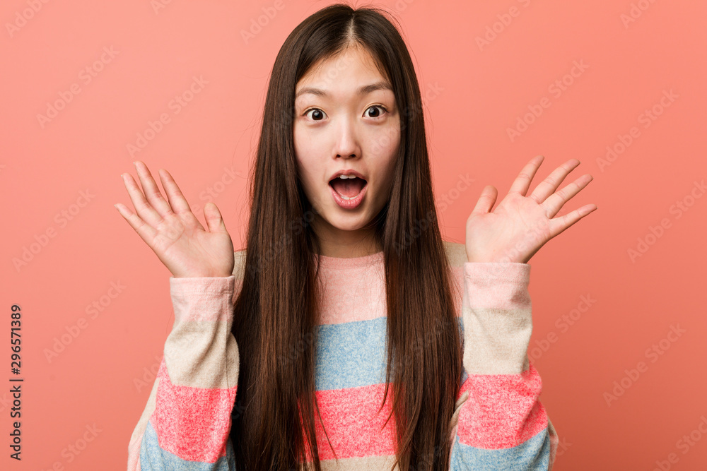 Fototapeta Young cool chinese woman surprised and shocked.