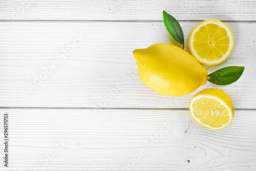 Lemons fruit on white table. Top view of juicy fresh lemon with leaves. - 296571753