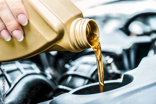 Fotografía  Woman hand pour motor oil to car engine