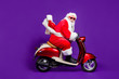 canvas print picture - Profile photo of fat santa role man rushing newyear party by bike private presents courier delivery wear sun specs and red x-mas costume isolated purple background