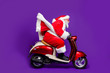canvas print picture - Photo of fat santa role man rushing newyear theme party by bike private presents courier wear sun specs and red x-mas costume isolated purple background