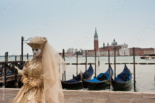 A masked woman for the Venice carnival in San Marco piazza, in the background the island of San Giorgio Maggiore. Italy