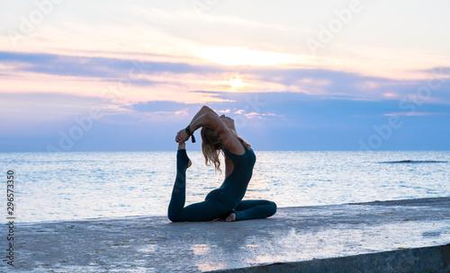 unrecognizable senoir woman with beautiful body doing yoga splits at sunrise on Wallpaper Mural
