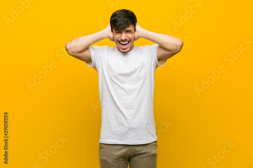 Photo  Young hispanic casual man covering ears with hands trying not to hear too loud sound