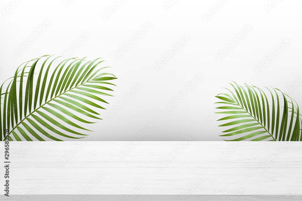 Fototapety, obrazy: white wooden table top with green palm leave for product advertisement display on white background