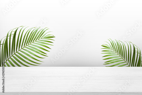 Recess Fitting Palm tree white wooden table top with green palm leave for product advertisement display on white background