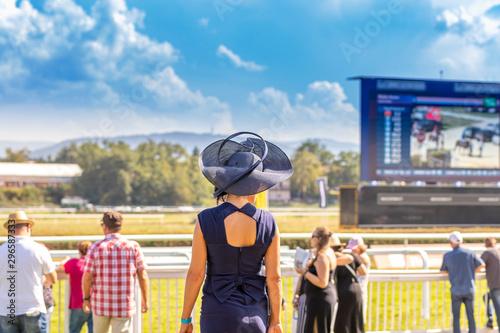 Frau mit blauen Hut steht an der Pferderennbahn Canvas Print