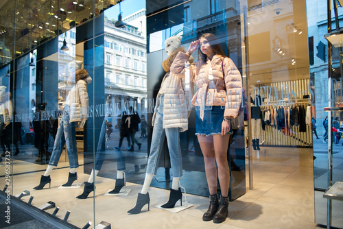 Young attractive woman posing in shopwindow near mannequins, Milan, Italy Canvas Print
