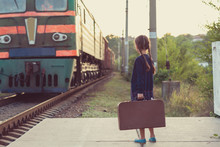 Beautiful Charming Little Girl With Pigtails Waiting For Train At Station Dressed Dark Blue Dress With Flowers And Blouse Holding Big Vintage Luggage. Young Traveler, Retro Stylization. Cute Kid