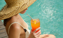 Girl In A Big Straw Hat Sitting At The Pool Edge And Holding A Cocktail Glass, Summertime Vacation Leisure Activity