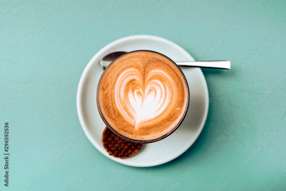 Fototapety, obrazy: high angle view and close up of a cappuccino cup with teaspoon and cookie against a green background