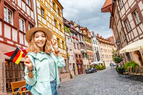 Obraz Young asian woman tourist traveling with german flag near the famous half-timbered street in Nuremberg old town - fototapety do salonu