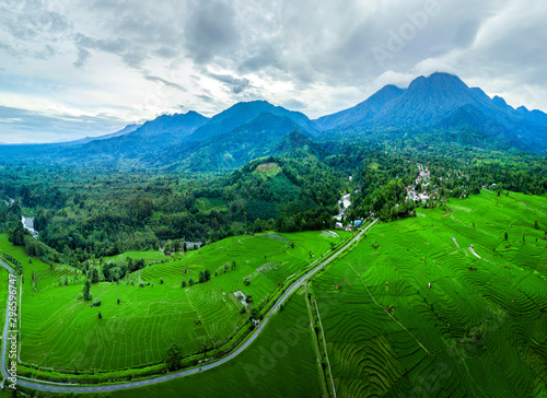 Valokuvatapetti aerial panoramic of extraordinary mountains with fog and clouds, incredible sky, the sun that shines brightly above the rice fields very dramatically during the daytime