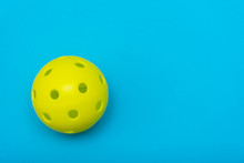 Bright Yellow Pickleball Or Whiffle Ball On A Solid Aqua Blue Flat Lay Background Symbolizing Sports And Activity With Copy Space.