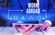 Leinwanddruck Bild - Word writing text Work Abroad. Business photo showcasing Immersed in a foreign work environment Job Overseas Non Local Male human wear formal work suit presenting presentation using smart device