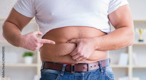 Fototapeta Man suffering from extra weight in diet concept obraz
