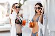 Two girls in swimwear posing with drink