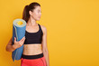 Close up portrait of young beautiful Caucasian woman standing and holding blue yoga mat in hand, ready for exercising in gym, wears stylish top and leggins, looking aside. Copy space for advertisment.