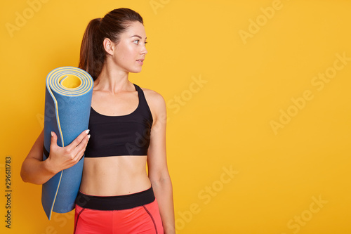 Close up portrait of young beautiful Caucasian woman standing and holding blue yoga mat in hand, ready for exercising in gym, wears stylish top and leggins, looking aside Obraz na płótnie