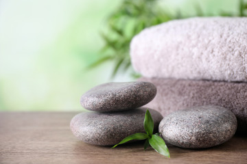 Composition with spa stones and towels on wooden table against blurred background. Space for text