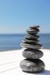 Leinwanddruck Bild - Stack of stones on wooden pier near sea, space for text. Zen concept