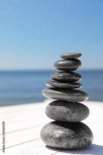 Foto auf Leinwand Zen Stack of stones on wooden pier near sea, space for text. Zen concept