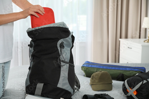 Fotografie, Tablou Woman packing different camping equipment into backpack at home, closeup