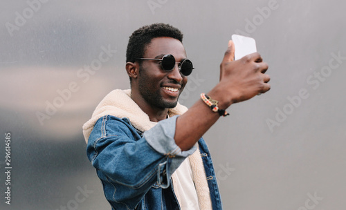 Fotografia  Portrait close up of happy smiling african man taking selfie picture by smartpho