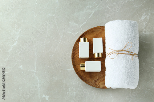Photo Top view of wooden tray with cosmetic bottles and towel on light grey marble table, space for text