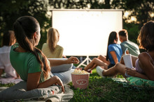 Young People With Popcorn Watching Movie In Open Air Cinema. Space For Text