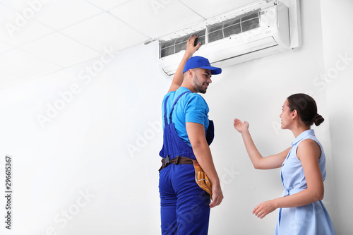 Fotografía  Professional technician speaking with woman about air conditioner indoors